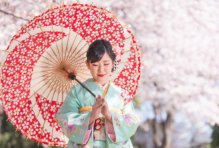 桜の木下で、振袖を着た女性が傘をさす様子