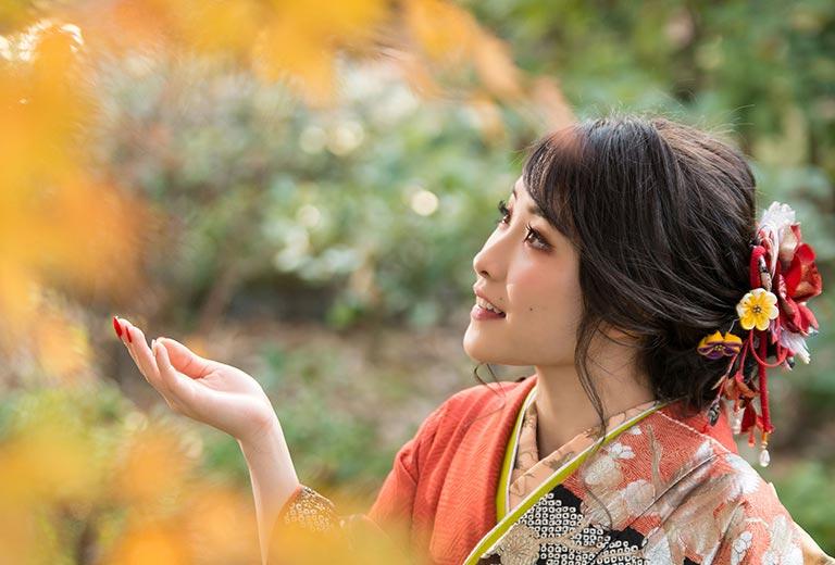 紅葉の下で、振袖を着た女性が笑顔の様子